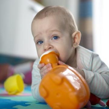Bébé portant un jouet à la bouche